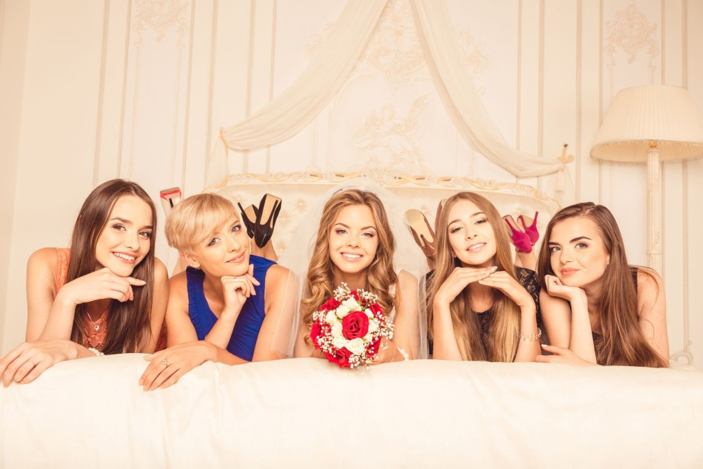 Cheerful girls celebrating a bachelorette party of bride lyiing on the bed