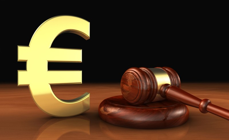 Cost of justice in EU concept with law lawyer and euro icon and symbol and a judge gavel on a wooden desktop .