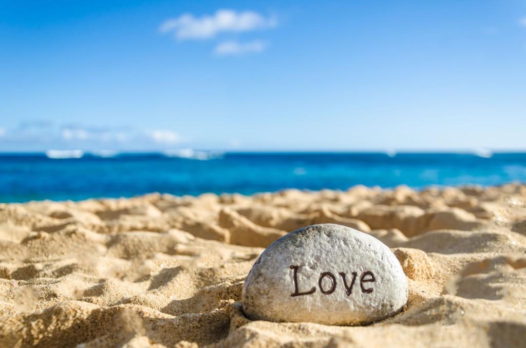 Sign love on the sandy beach near ocean in Hawaii Kauai - Valentine's day romantic concept