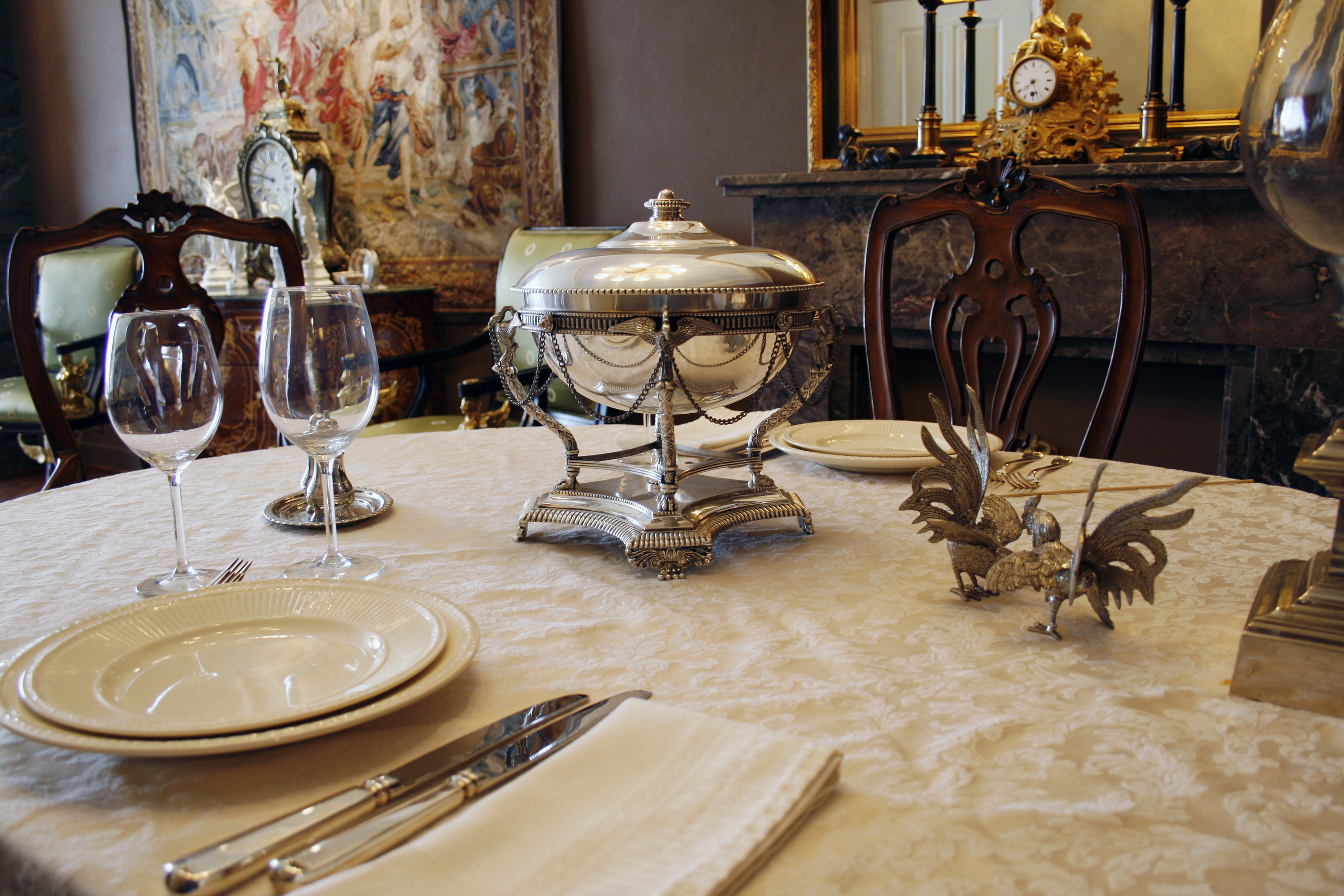 beautifully set table with antique silverware and silver soup bowl